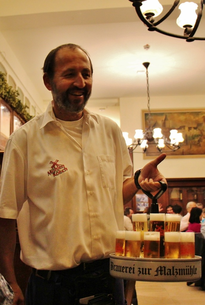 Kobe waiter carrying tray of Kolsch beer in Cologne, Germany