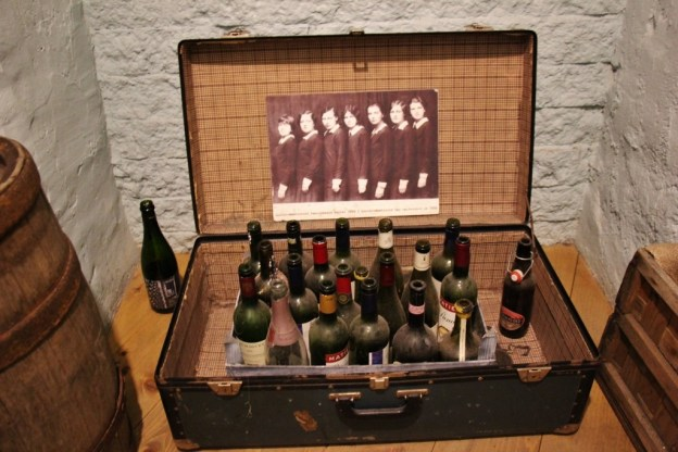 Dusty wine bottles displayed in old suitcase at Museum of Estonian Drink Culture in Tallinn, Estonia