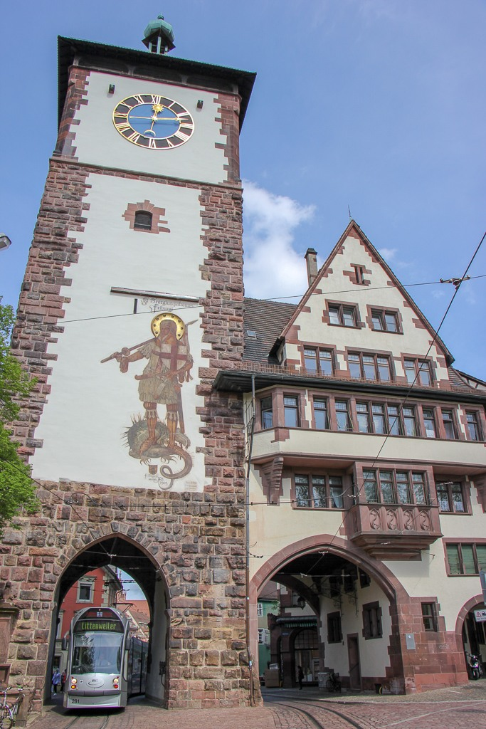 Tram passing under Schwabentor Tower in Freiburg, Germany