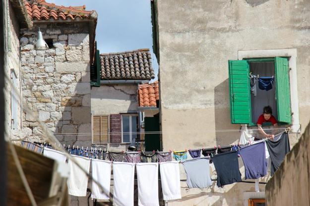 Women hangs laundry from window in Diocletian's Palace, Split, Croatia