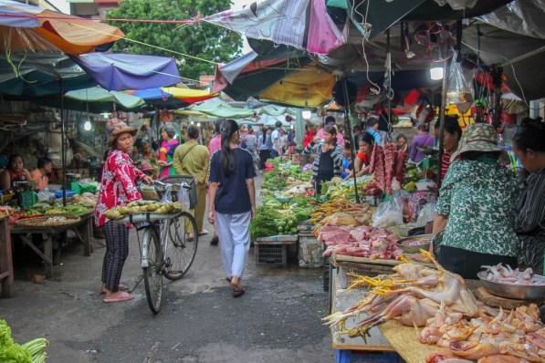 Shopper on bike peruses produce and chicken for sale at Old Market in Phnom Penh, Cambodia