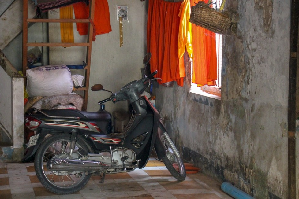 Cyclo parked next to drying saffron monk robes in temple in Phnom Penh, Cambodia