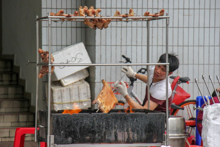 Street food cook grills meat over flame in Singapore