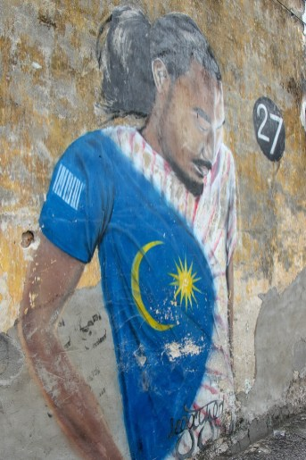 Man wearing Malaysia shirt Street Art mural in Geroge Town, Penang, Malaysia