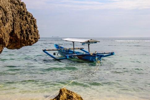 Traditional Bali Boat in water at Padang-Padang Thomas Beach in Uluwatu, Bali, Indonesia