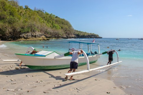 Men push local boat into Crystal Bay on Nusa Penida, Bali, Indonesia