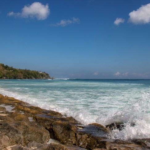 Waves crash on rocks at Padang-Padang Thomas Beach in Uluwatu, Bali, Indonesia