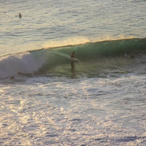 Surfer rides wave in Uluwatu, Bali, Indonesia