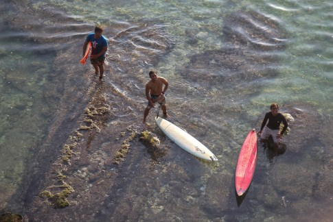Three surfers stand in shallow water at Suluban Beach in Uluwatu, Bali, Indonesia