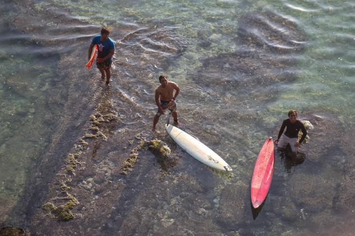 Three surfers stand in shallow water at Suluban Beach in Uluwatu, Bali, Indonesia
