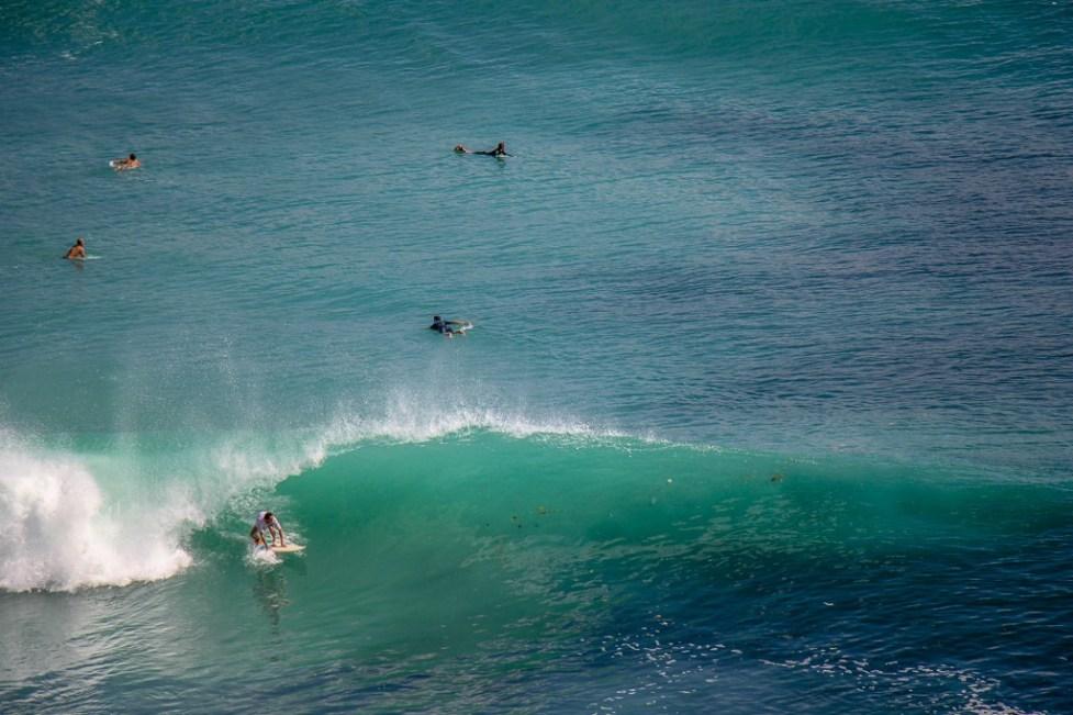 Surfer riding big wave at Padang-Padang Thomas Beach in Uluwatu, Bali, Indonesia