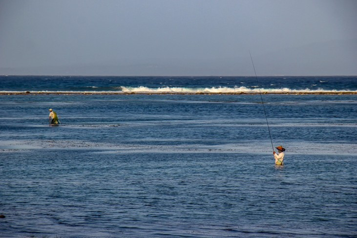Fisherman in water at sunset in Sanur, Bali, Indonesia