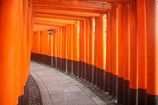 Pathway covered with orange torii gates at Fushimi Inari Shrine in Kyoto, Japan