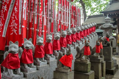 Fox statues and red flags at Toyokawa Inari Shrine in Tokyo, Japan