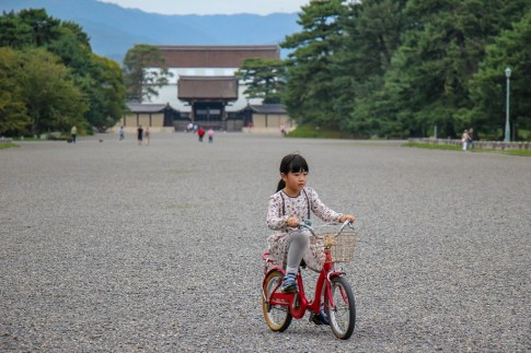 Girl rides bike at Kyoto Imperial Palace in Kyoto, Japan