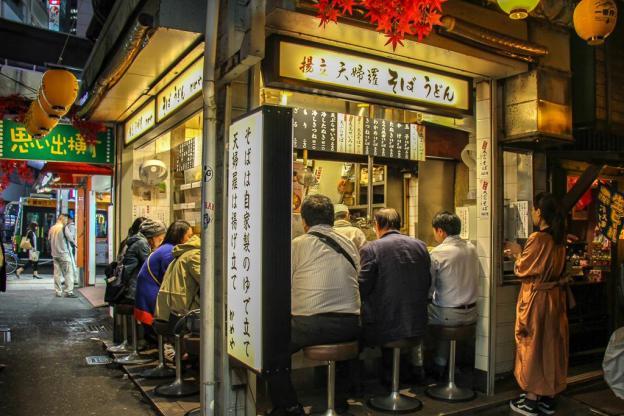 Corner restaurant stall filled with patrons at Omoide Yokocho Memory Lane in Tokyo, Japan
