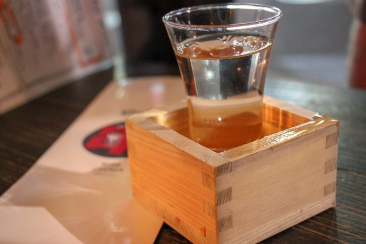 Sake served in a wooden box at Joumon Roppongi in Tokyo, Japan