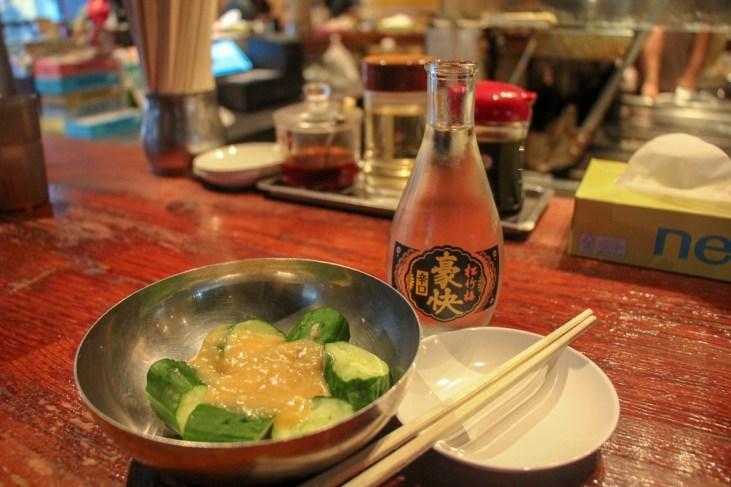Cucumber salad and sake at Harajuku Gyozaro in Tokyo, Japan