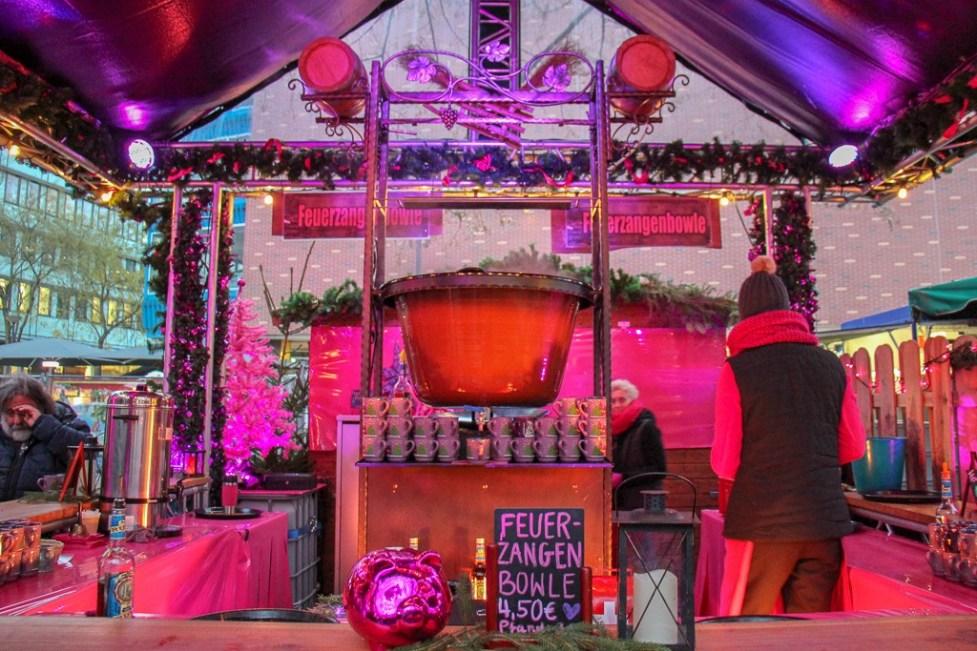 Preparing Feuerzangenbowle at Pink Christmas Market in Frankfurt, Germany