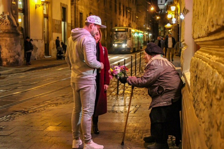 Couple buys flowers from old woman on a street corner in Lviv, Ukraine