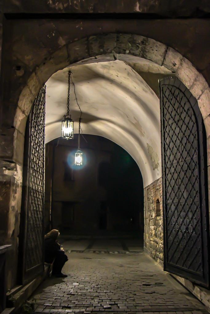 Woman sits in passageway at night in Lviv, Ukraine