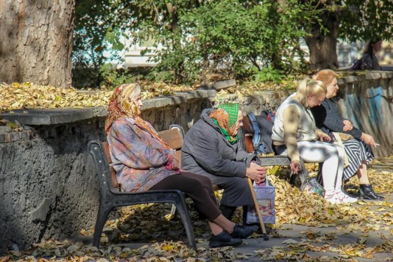Women sit on park benches in Lviv, Ukraine