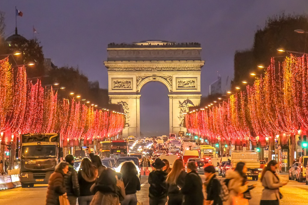 Red Christmas Lights decorate trees on Champs Elysees leading to Arc de Triomphe in Paris, France