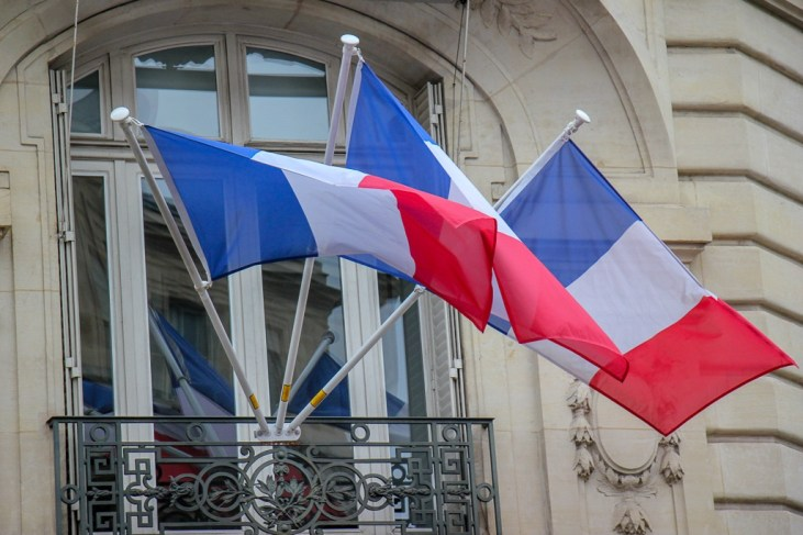 Three French flags fly from balcony in Paris, France