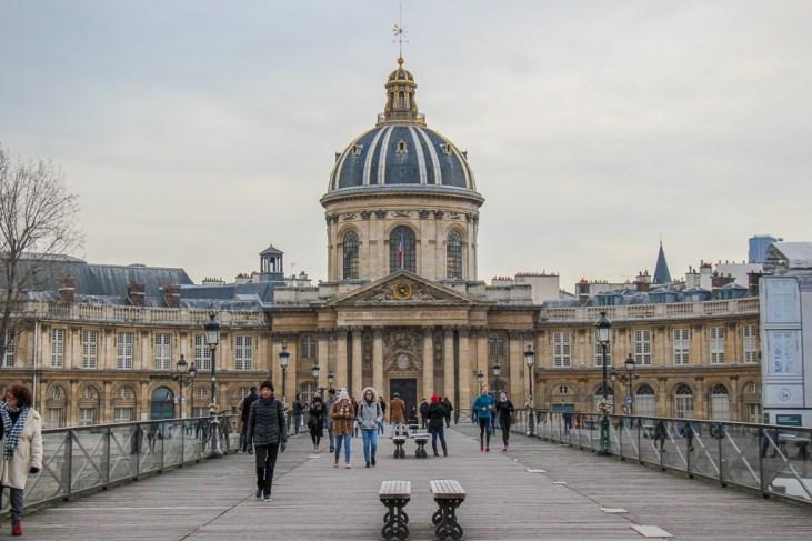 Walking across Pont des Arts Bridge in Paris, France