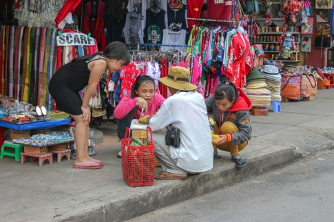 Vendors eat on sidewalk at Central Market in Hoi An, Vietnam