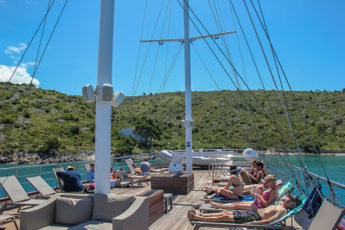 People lounging in chairs on top deck of Almissa on Sail Croatia Adriatic Sea Cruise