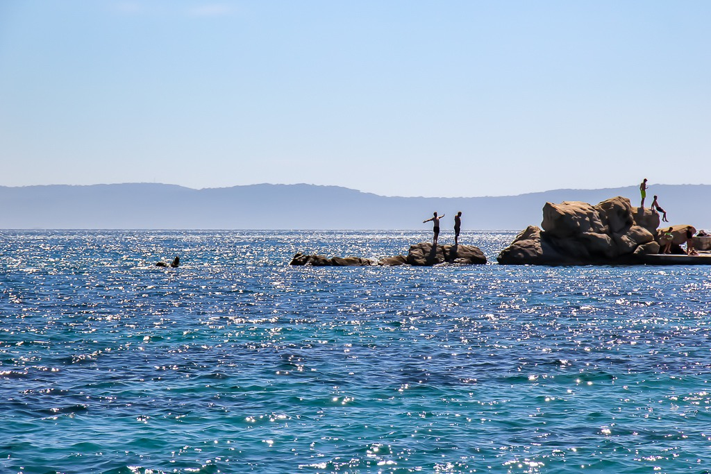 Boys explore the rocks on the western side of Bacvice Beach in Split, Croatia
