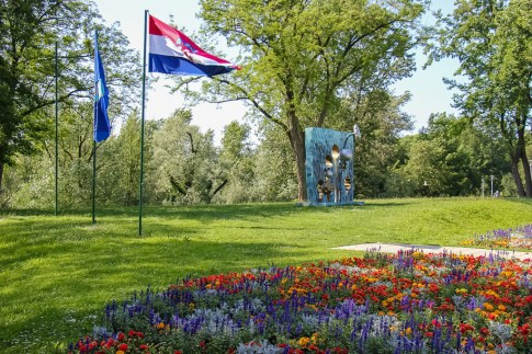 Croatian flag flies over flowerbed in Bundek Park in Zagreb, Croatia
