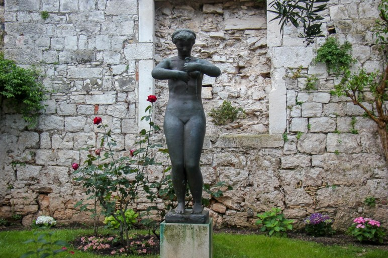 Statue of woman with flower in garden in Old Town on Korcula Island, Croatia