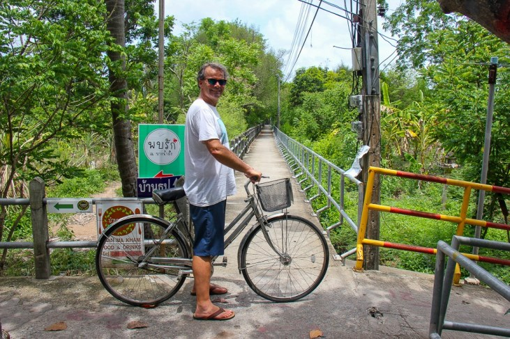Man stands with bicycle on bike paths in Bang Kachao in Bangkok, Thailand