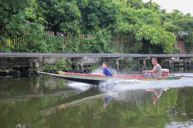 Man and boy on boat in canal in Bangkok, Thailand
