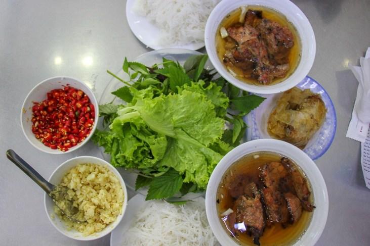 Bowls of Bun Cha and accompaniments at Bun Cha Huong Lien in Hanoi, Vietnam