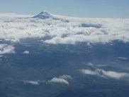 Volcano peeking through the clouds. Squint and you can see the ground below the clouds, too.