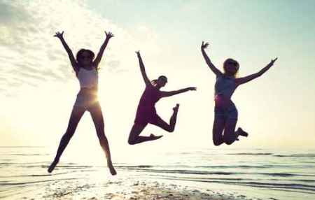 happy female friends dancing and jumping on beach