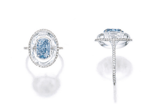 Centring on a cushion-shaped fancy vivid blue diamond weighing 2.05 carats, embedded in a carved oval rock crystal, bordered by brilliant-cut diamonds extending to the shank, mounted in 18 karat white gold.
