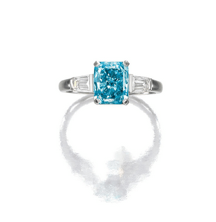 Set with a fancy vivid green-blue cut-cornered rectangular mixed cut diamond weighing 2.68 carats, between trapeze diamond shoulders, mounted in platinum.