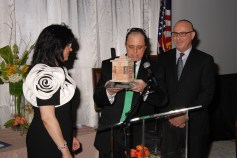 Rabbi Mordechai Shifman giving a gift to honorees, Gary and Rochelle Finder