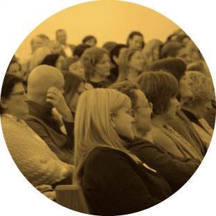A large group of adults sitting in a room, engaged and focused on listening to somebody speaking to them.