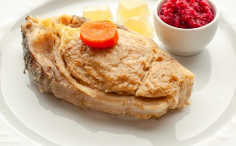 """Gefilte fish,"" stuffed carp steaks with ""chrain,"" beet horseradish and jellied broth on a plate.."