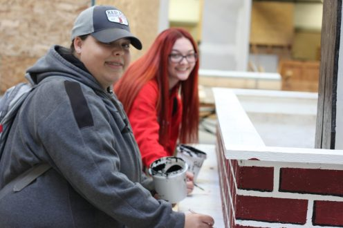 Abigail Slevoski, a junior, of Georgetown, left, paints the bricks that line the bed of the float with Julia Chadwick, a junior from Haverhill. (Courtesy Photo Whittier Tech)