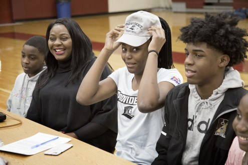 Grace Efosa puts on a Providence College hat after signing and accepting a full, four-year basketball scholarship to Providence College on Wednesday, Nov. 13. From left: Angel Efosa, 11; Grace Efosa's mom, Esosa Omorodion; Grace Efosa, 17; and Junior Efosa, 16.  (Courtesy Photo Whittier Tech)