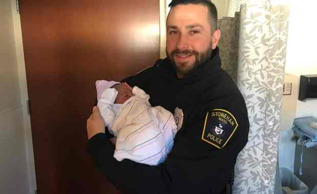 Stoneham Police Officer Michael Colotti holding the baby he helped deliver on Thanksgiving (Stoneham Police/Courtesy Photo)