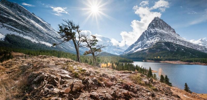 snow mountain colorful lake and sunburst