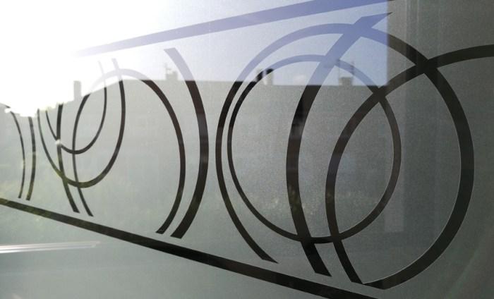 Adhésif dépoli gris avec motif cercles posé sur une fenêtre