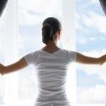 Une femme ouvre ses rideaux pour laisser passer le soleil